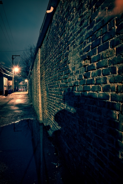 Scary shadow on a vintage brick wall in a dark, gritty and wet C